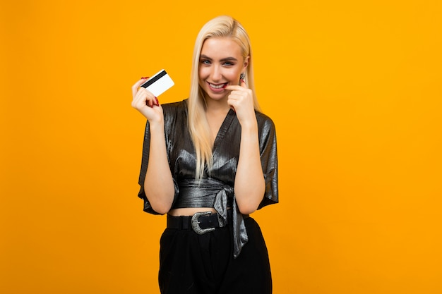 Portrait of a girl with a card with a mockup for shopping on a yellow wall