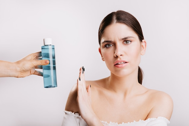 Portrait of girl with displeased facial expression on white wall with micellar water. woman without makeup against use of cosmetics.