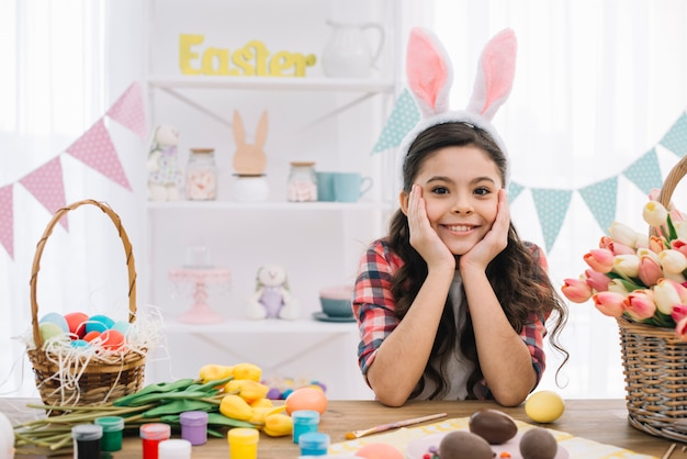 Portrait of a girl with easter eggs; paint and tulips flowers on table