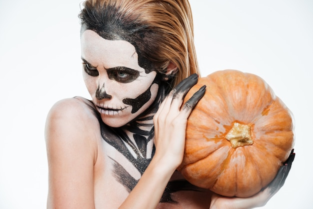 Portrait of girl with fearful halloween makeup holding pumpkin over white background