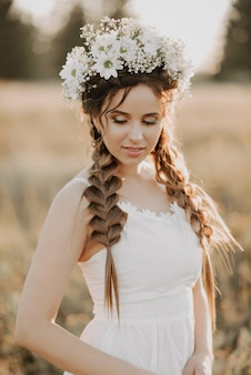 Portrait of girl with flower wreath and braids in white dress in summer field at sunset