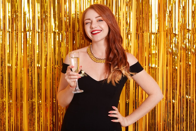 Portrait of girl with glass of champagne, posing against wall decorated with golden tinsel, attractive lady wearing black dress, red haired smiling female celebrating holiday.