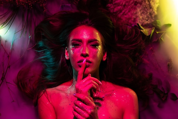 Portrait of a girl with glitter on her body in pink creative light. the girl lies in flowers and smoke.
