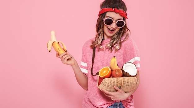 Portrait of a girl with healthy food, fruits, on a pink wall