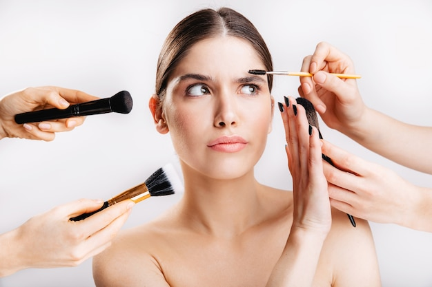 Portrait of girl with healthy skin on white wall. woman doesn't want to do makeup and removes from her face brushes.
