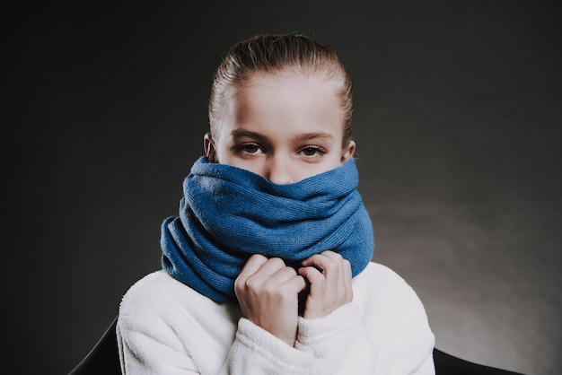 Portrait girl with knitted scarf around neck.