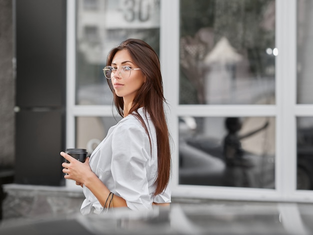 Portrait of girl with long dark hair drinking coffee, looking at camera.