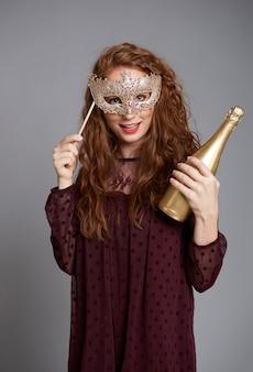 Ritratto di ragazza con maschera in maschera e champagne