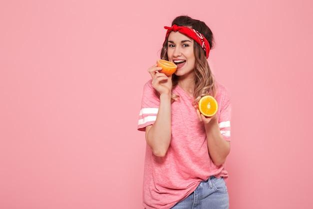Ritratto di una ragazza con le arance in mano, su uno sfondo rosa