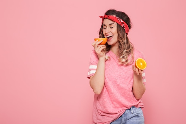 Portrait of a girl with oranges in hand, on a pink wall