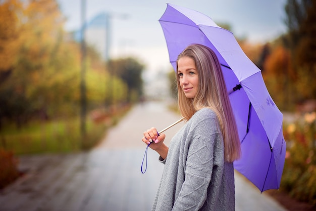 Portrait of a girl with a purple umbrella in an autumn park