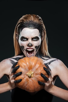 Portrait of girl with scared skeleton makeup holding pumpkin and shouting over black background