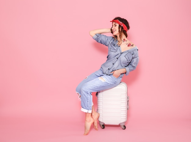 Portrait of a girl with a suitcase on a pink wall