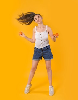 Portrait of a girl with tangerines on a yellow background
