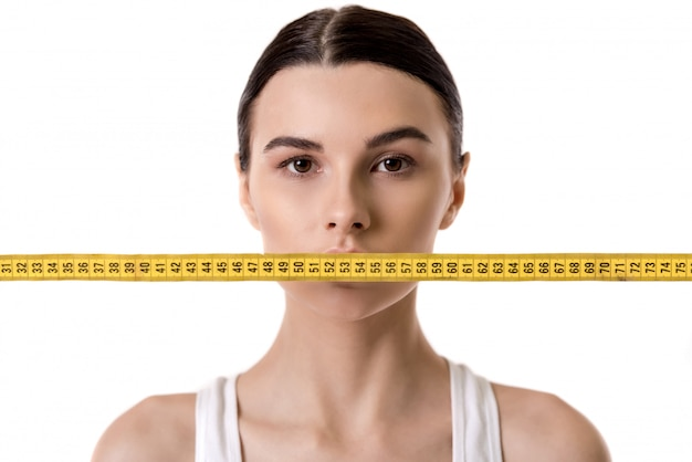 Portrait of girl with a tape measure in front of her mouth. diet concept