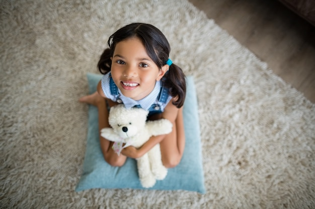 Portrait of girl with teddy bear sitting in living room