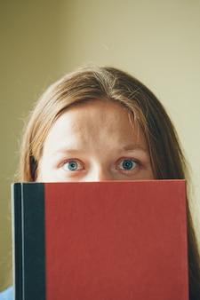 Portrait of a girl: a woman looks out from behind a book. the student uses literature as a space for writing. eyes close up