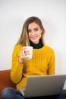 Portrait of a girl working at home. holding a mug and looking at camera.