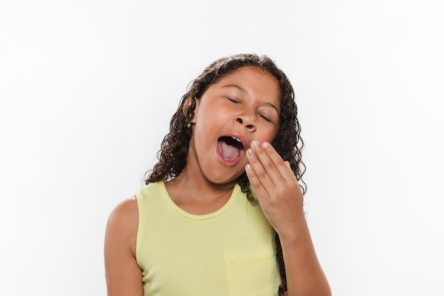 Portrait of a girl yawning on white background