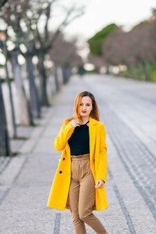 Portrait of a girl in a yellow coat walking in street. female fa