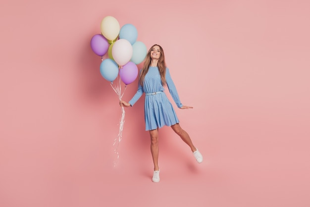 Portrait of girlish lady with many colorful air balloons on pink background