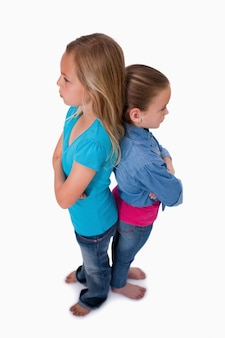 Portrait of girls standing back to back