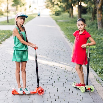 Portrait of girls standing on kick scooter in the park