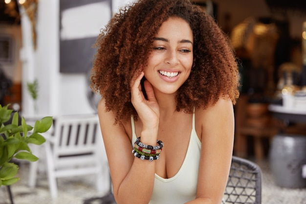 Portrait of glad african american female has positive smile, has bushy hairstyle looks with dreamy expression away sits against cafeteria interior.