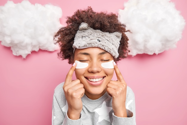 Portrait of glad afro american woman points at beauty patches under eyes enjoy skin care procedures dressed in pajama soft sleepmask smiles gently poses indoor against rosy wall with clouds above