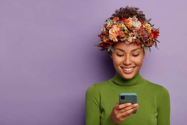 Portrait of glad autumn model wears decorative autumnal wreath, focused in smartphone device, reads good news online, has happy face expression, models over purple studio wall.