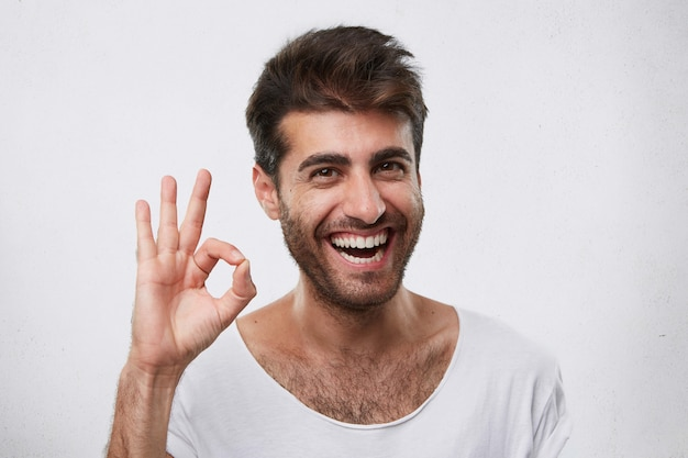 Portrait of glad bearded man with stylish hairstyle showing ok sign expressing his agreement. young handsome businessman showing his success and rejoicing his triumph at work gesturing