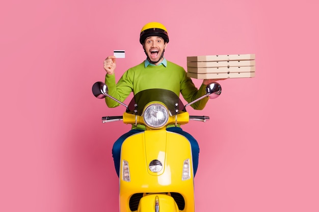 Portrait of glad guy riding moped holding in hands bank card