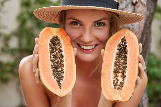 Portrait of glad lovely woman poses naked, wears summer hat, holds organic exotic papaya