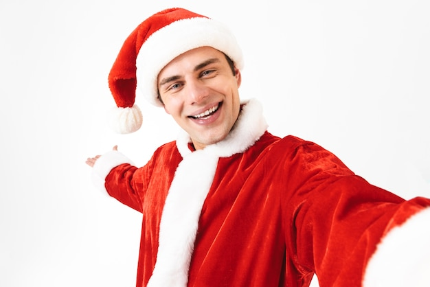 Portrait of glad man 30s in santa claus costume and red hat laughing while taking selfie photo