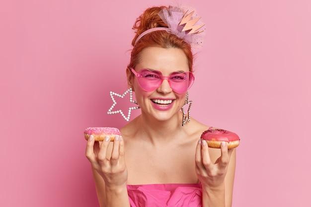 Il ritratto della giovane donna felice della testarossa sorride positivamente essendo di buon umore