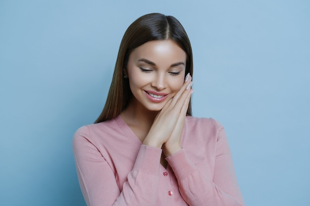 Portrait of glad shy woman keeps hands pressed together near face, isolated on blue background