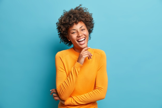 Portrait of glad young woman laughs happily keeps hand on chin expresses positive emotions smiles broadly has carefree expression wears orange jumper isolated over blue wall