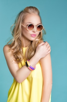 Portrait of glamorous beautiful blond woman in sunglasses and yellow shirt on blue background. carefree summer.