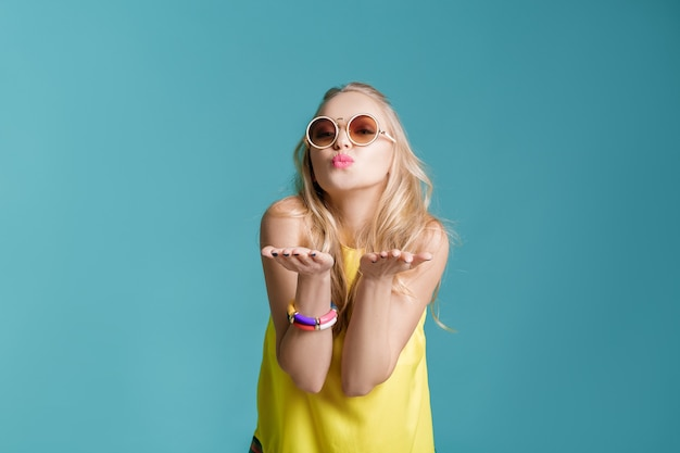 Portrait of glamorous beautiful blond woman in sunglasses and yellow shirt on blue background. girl sending air kiss