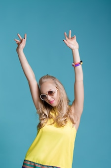 Portrait of glamorous beautiful blond woman in sunglasses and yellow shirt dancing on blue background. carefree summer.