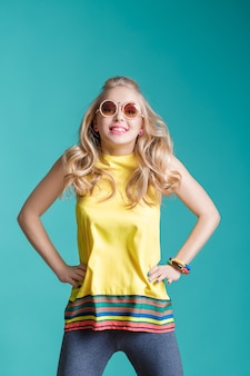 Portrait of glamorous beautiful blond woman in sunglasses and yellow shirt jumping on blue background. carefree summer.