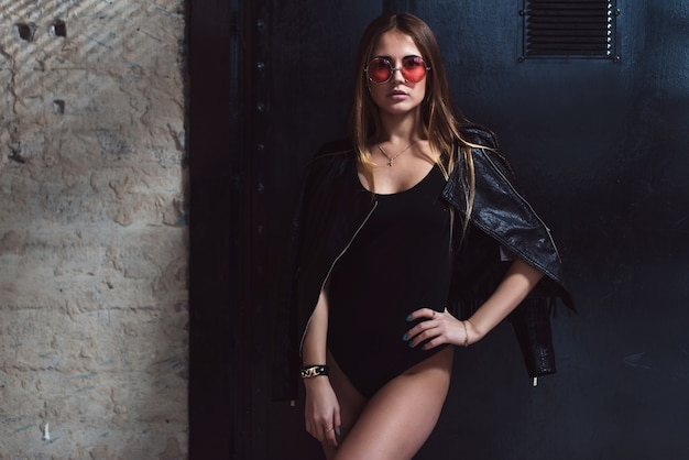 Portrait of glamorous caucasian female model in trendy rock style wearing black bodysuit, leather jacket and pink sunglasses standing against black background