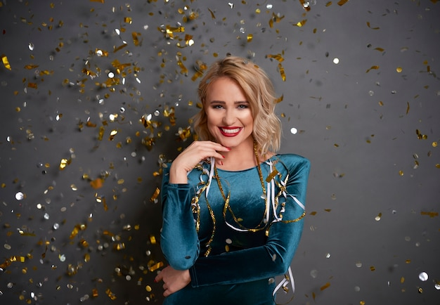 Portrait of glamorous woman under shower of confetti
