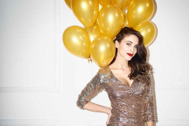 Portrait of glamorous woman with golden balloons