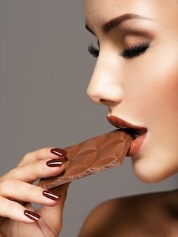 Il ritratto della bella donna di fascino mangia il cioccolato dolce