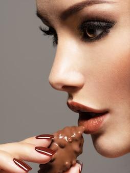 Ritratto di donna bella glamour tiene e mangia caramelle al cioccolato. foto in stile colore marrone