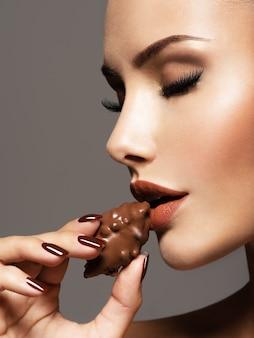 Ritratto di donna bella glamour tiene e mangia caramelle al cioccolato.