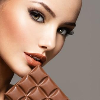 Ritratto di fascino la bella donna con le unghie marroni tiene la barra di cioccolato