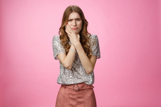 肖像画の魅力的な女の子は不快な歯痛を感じる頬の痛みを伴う虫歯に触れるホットコーヒーを飲む...