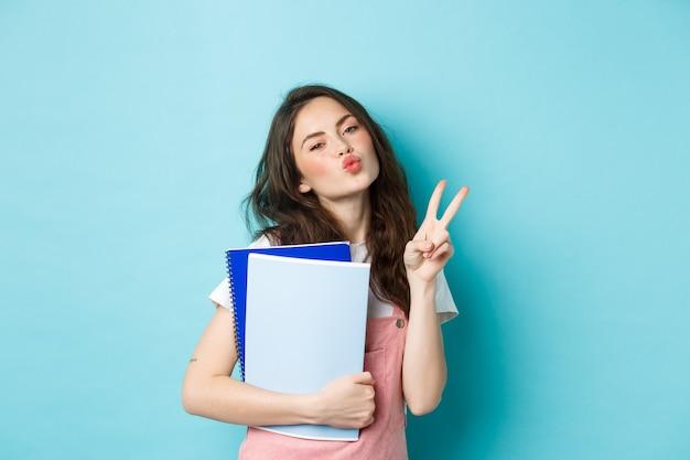 Ritratto di ragazza glamour che mostra il viso baciante e il segno v, porta il materiale per i compiti dei quaderni, in piedi su sfondo blu